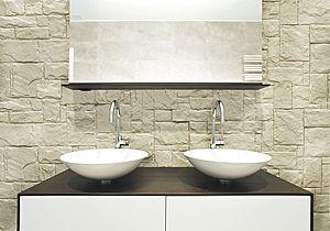 Rivestimento del paramento murario del bagno con pannello in pietra calcarea chiara, in contrasto il legno wengè del piano d'appoggio della coppia di lavabi.