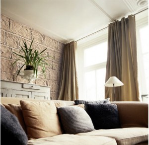 Zona living con paramento murario in pietra tagliata color ocra.