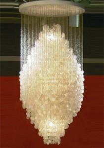 Lampada a sospensione con un grande cluster di dischi madre-perla. Attaccato da catene di anelli metallici di piccole dimensioni. Montato su piatto bianco soffitto in legno.