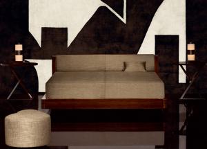 Una soluzione del letto Botticelli affiancato da due comodini molto semplici nelle geometrie. (ArmaniCasa)