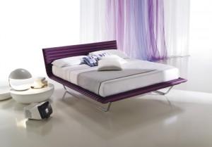 Zona notte in cui il letto e i tessuti color lilla, giocano un ruolo importante per definire il colore dell'ambiente. (Ciacci Kreaty)
