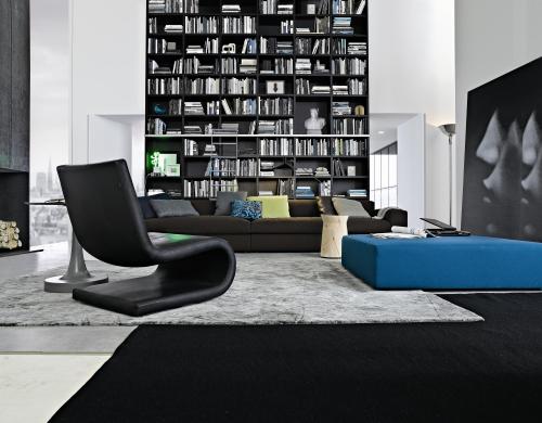 Esempio di un'interno in cui pur prevalendo tonalità neutre dal bianco al grigio la presenza di una seduta blu e dei cuscini colorati conferiscono carattere e personalità (Poliform).