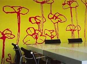 Soluzione per una tappezzeria murale dalle tinte decise giallo con  grandi fiori rossi ideale in una zona living.