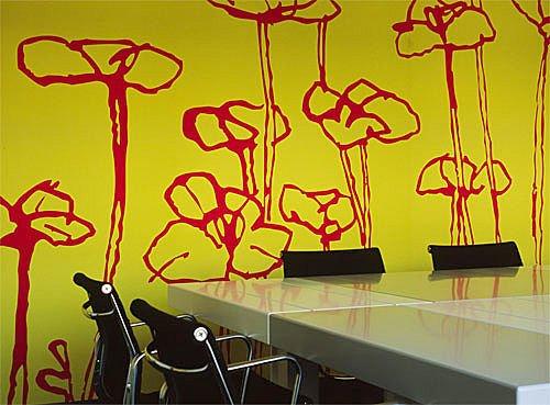 Soluzione per una tappezzeria murale dalle tinte decise giallo con grandi fiori rossi.