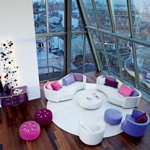 Zona living con gradazioni dalle tinte viola e fucsia definiti dalle tappezzerie a contrasto il bianco del divano.(Roche Bobois)