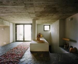 Interno che conferisce calore grazie ai materiali naturali usati per le pavimentazioni - pietra e legno- in contrasto al rigore delle geometrie squadrate ed essenziali del cemento a vista.