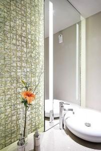 Bagno con piastrelle a mosaico in madreperla e vetro.
