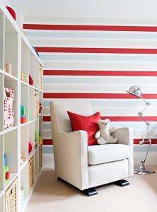 Righe orizzontali in tonalità chiare in un cui spicca la linea rossa richiamata da elementi di finitura come il cuscino.